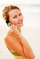 Pretty young female using a cellphone for communication while at the beach