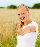 Happy beautiful young woman showing thumbs up at a field