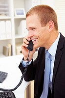 Portrait of a smiling young business man communicating on telephone