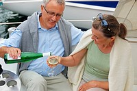 Mature man refilling wife´s champagne glass while on a sailboat