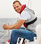 Portrait of a happy young guy wearing a life jacket sitting isolated in a sailboat at sea