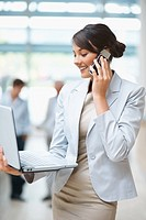 Happy young business woman talking on cellphone and using laptop