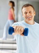 Portrait of a happy middle aged man working out with a dumbbell at the gym