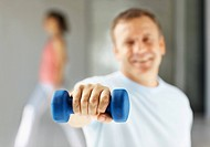 Man using a dumbbell to work out at the gym with the focus on his hand
