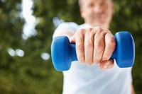 Closeup mid section of a blue dumbbell being held by a man outdoors