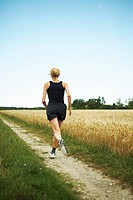 Woman jogging in an open landscape, Sweden.
