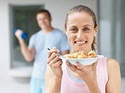Pretty middle aged woman eating a bowl of fruits with a man working out at the gym