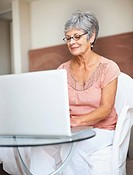 Portrait of a pretty senior woman using a laptop computer at home