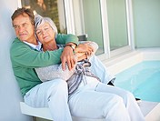 Smiling elderly couple on a vacation sitting together by the swimming pool
