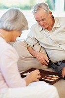 An old couple playing a game of backgammon at home