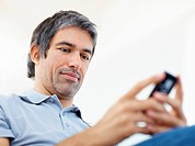 Closeup of a casual businessman typing text message on his cell phone