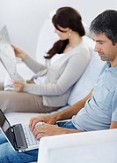 Closeup of a casual man working on laptop and woman reading newspaper _ Indoors