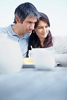 Closeup of a mature couple reading newspaper while having there breakfast