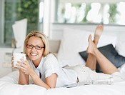 Portrait of smiling and attractive middle aged lady lying on bed holding a coffee cup