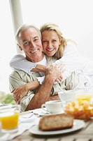 Happy romantic mature woman embracing her husband at breakfast table