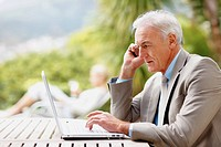 Senior business man using laptop and cellphone outdoors with a person at the background