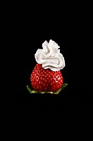A strawberry with whipped cream on top.