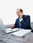 Serious senior business man using a laptop while on phone
