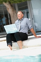 Happy successful business man enjoying at the swimming pool using a laptop
