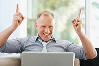 Happy middle aged business man using a laptop hands raised in excitement