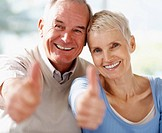 Success _ Portrait of a older couple showing thumbs up