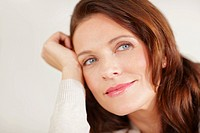 Closeup of a cute middle aged woman smiling thoughtfully