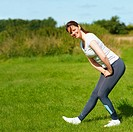 Healthy Lifestyle: Young woman doing leg stretches in park with a smile