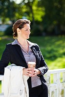 Happy mature business woman by a railing at park with a disposable coffee