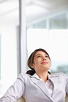 Happy young business woman looking upwards and smiling