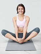 Portrait of a happy fitness woman sitting on mat and practicing yoga