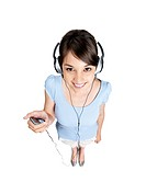 Top view of a smiling young woman listening to music on headphones on white background