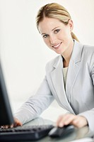 Portrait of a lovely young business woman using a computer against white background