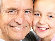 Closeup portrait of a small girl with her grandfather smiling together