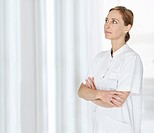 Middle aged female nurse with hands folded and looking at copyspace