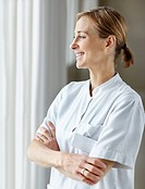 Happy Caucasian nurse with hands folded and looking out the window