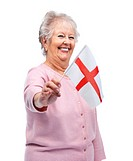 Portrait of a happy pretty old woman holding an English flag isolated over white