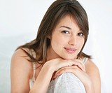 Closeup portrait of a beautiful young woman sitting comfortably over white background