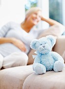 Happy middle aged pregnant female with teddy bear sitting on couch