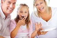 Closeup portrait of cute little girl eating cake with her parents