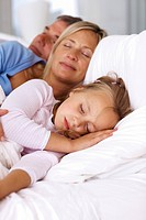 Sweet family sleeping peacefully together in a bedroom _ Indoor