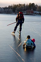 Man skating with children in a little sledge, Sweden.