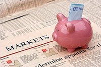 pink piggy bank with 20 euro note sitting on a copy of the financial times newspaper money markets section in the uk