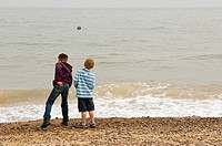 two boys 6 & 10 throwing stones into the sea on a UK beach