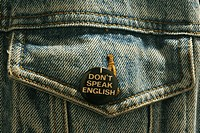 button saying ´I don´t speak English´ on pocket of blue jean jacket