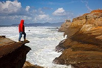 Pacific City, Oregon, United States Of America, A Man Standing On The Edge Of A Cliff Along The Coast At Cape Kiwanda