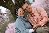 Portland, Oregon, United States Of America, A Couple Sitting Under A Cherry Blossom Tree In Spring