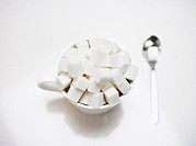 Coffee cup filled with sugar cubes