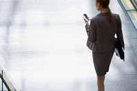 Businesswoman walking and looking down at cell phone