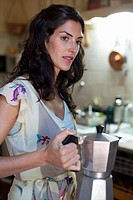 Woman holding a coffee maker
