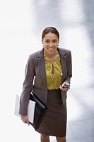 Smiling businesswoman holding paperwork and cell phone
